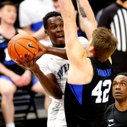 Weber State Wildcats guard Seikou Sisoho Jawara (5) crashes into Brigham Young Cougars center Richard Harward (42) as BYU and Weber State play an NCAA basketball game at Vivint Smart Home Arena in Salt Lake City on Wednesday, Dec. 23, 2020.