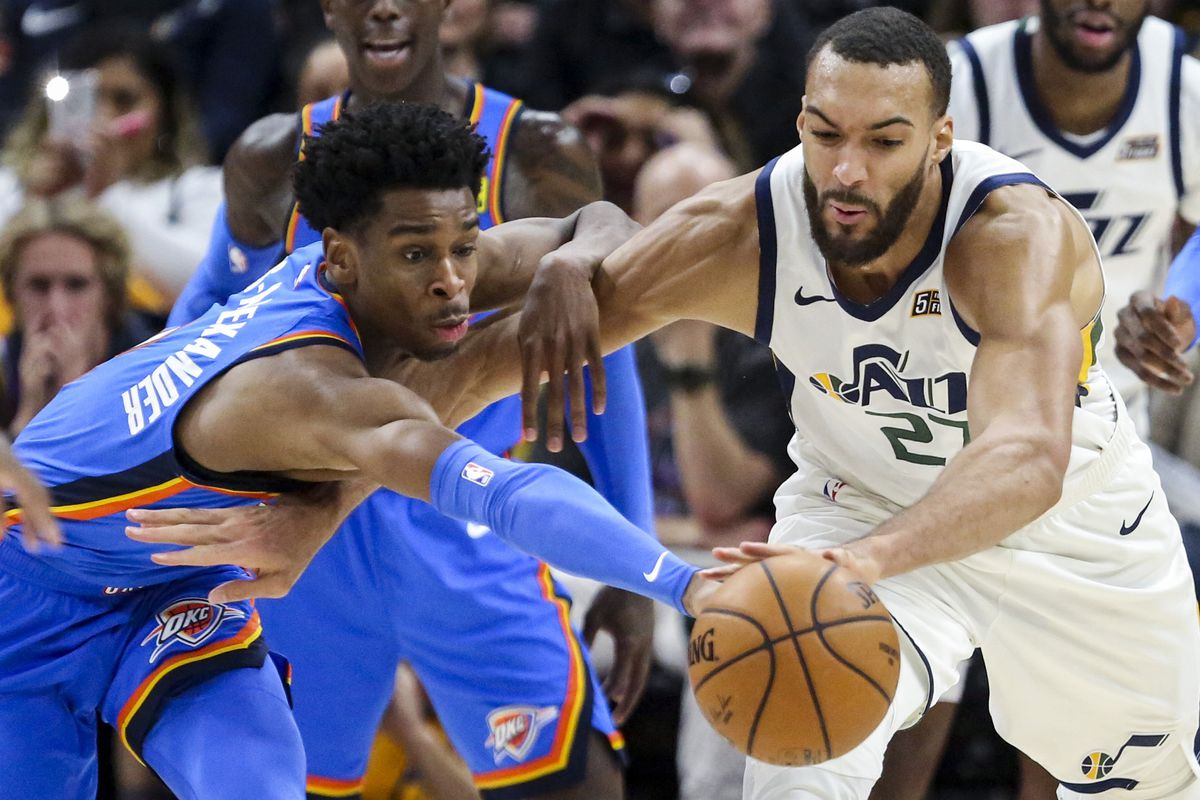 Utah Jazz center Rudy Gobert (27) and Oklahoma City Thunder guard Shai Gilgeous-Alexander (2) chase down a loose ball during the second half of a NBA basketball game at Vivint Smart Home Arena in Salt Lake City on Monday, Dec. 9, 2019. The Jazz fell to the Thunder 104-90.