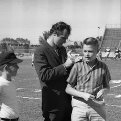 1963-Burt Reynolds signing autograph for fan at FSU's annual spring game in Tallahassee.