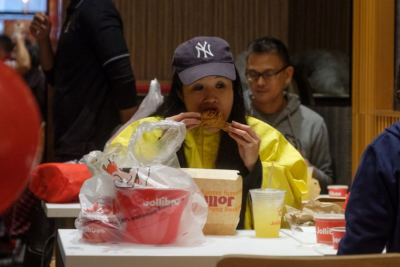 A female customer takes a bite of Chickenjoy.