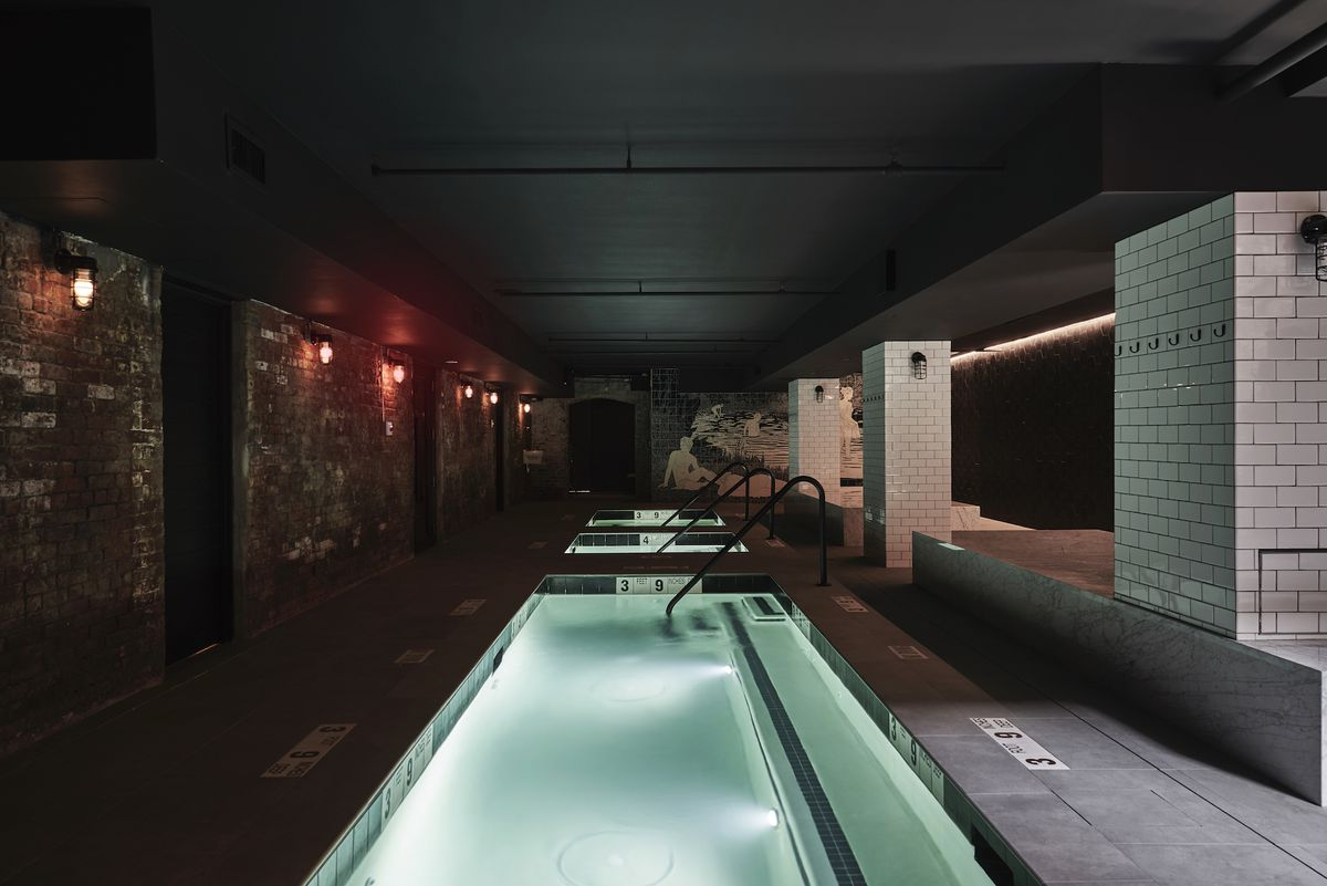 A series of pools are shown in a dark setting, with gray tile, and white tiled walls.