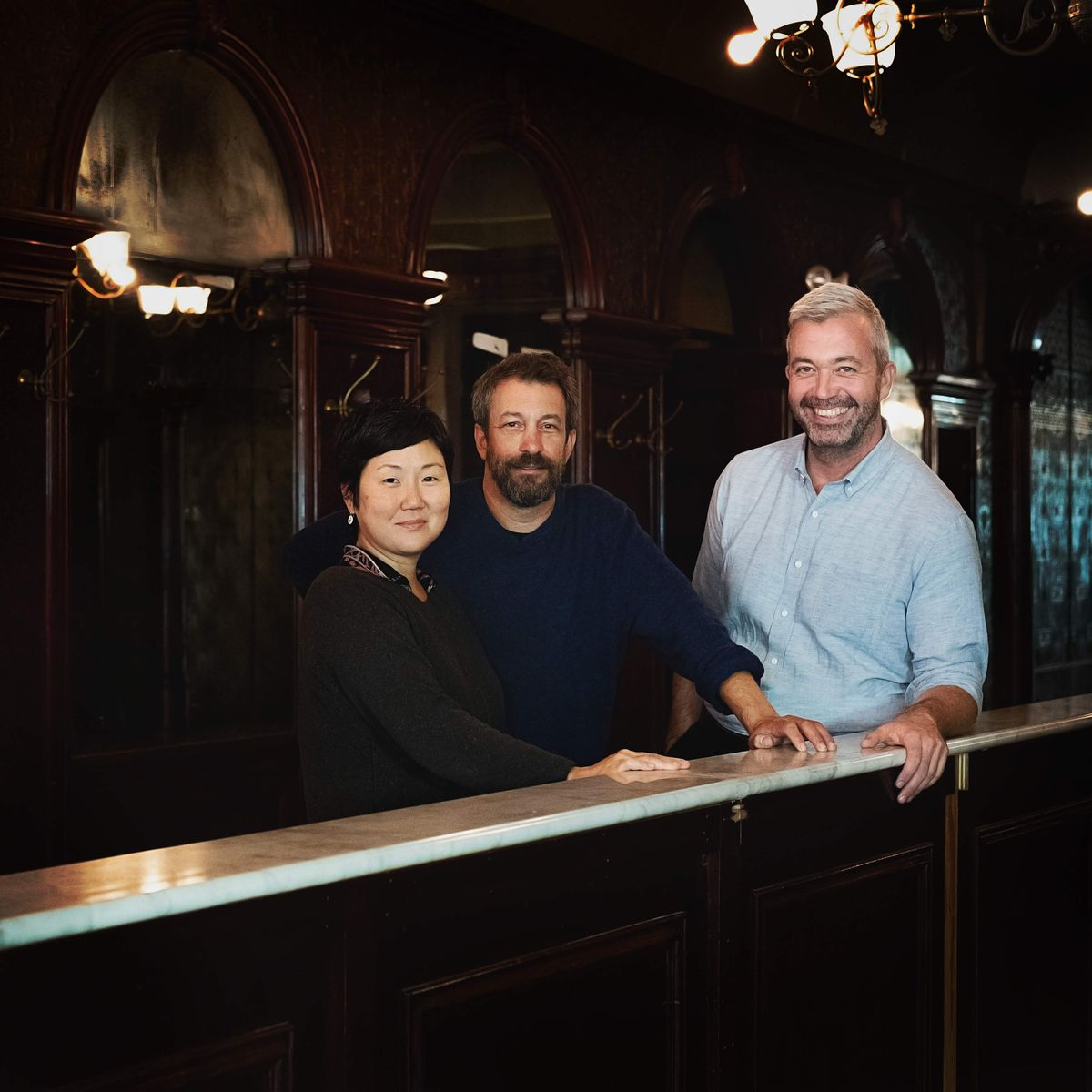 Sohui Kim, Ben Schneider, and St. John Frizell stand at the bar in a wood-lined space