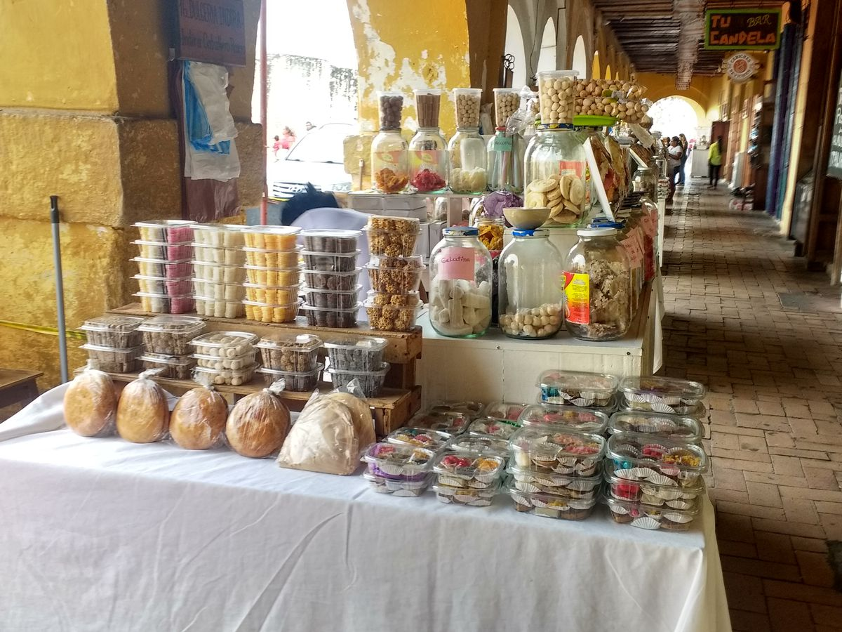 Tables loaded with jars and plastic boxes of sweets sit beneath archways with the sun shining beyond