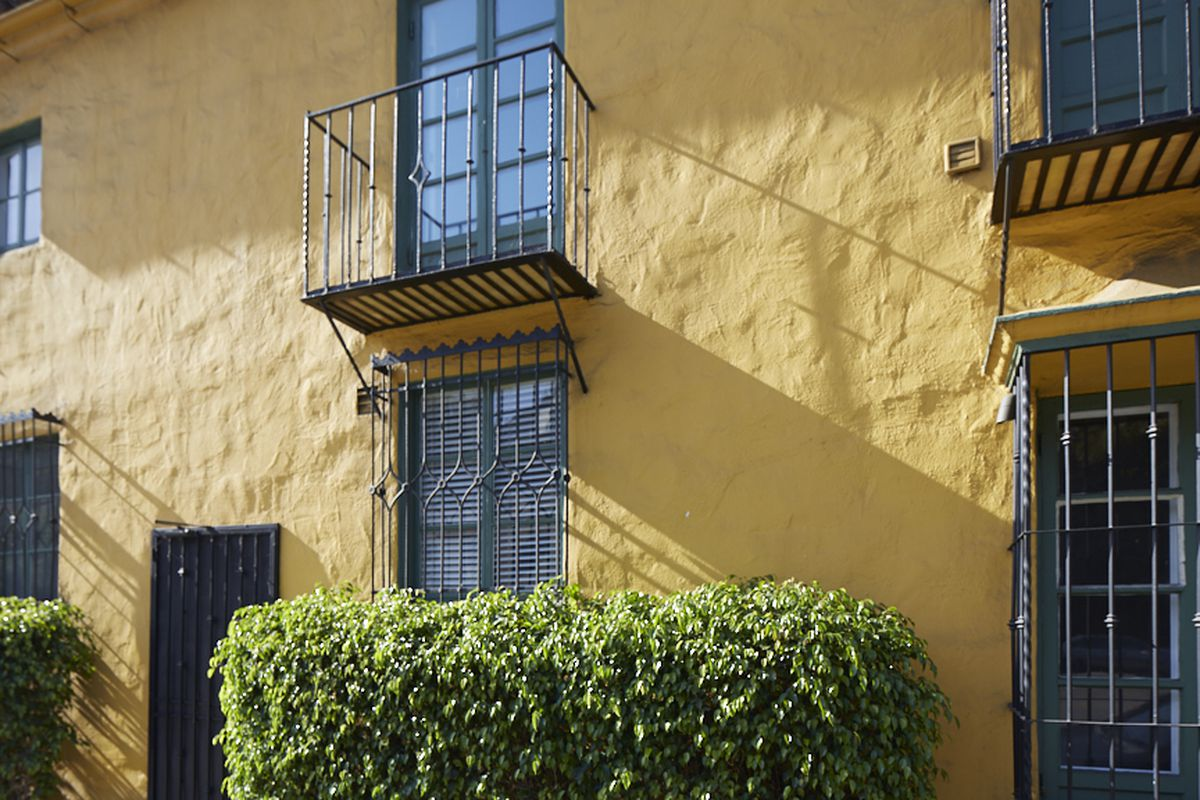 Close-up of a yellow stucco facade with Juliet-style balconies with wrought iron railings.