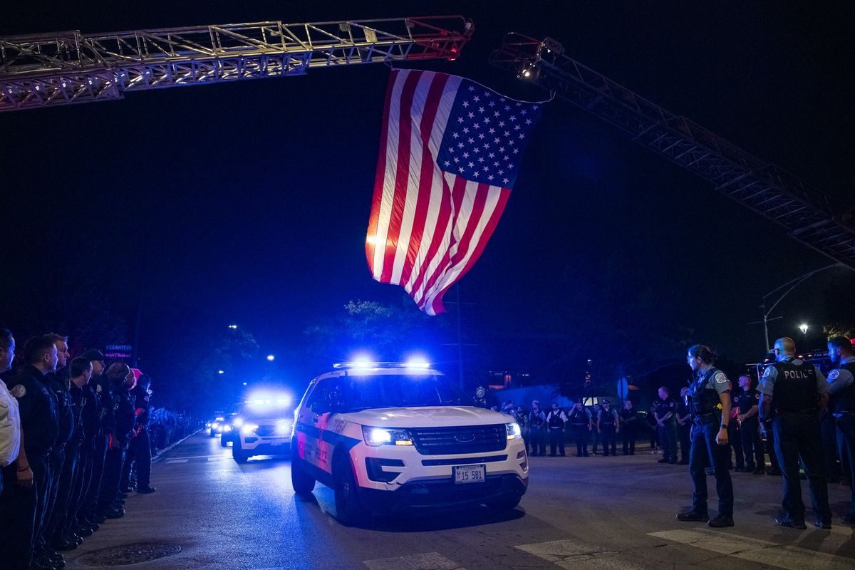 A Chicago police procession for a police officer who was shot and killed earlier during a traffic stop at 63rd and Bell drives by the Cook County Medical Examiner's Office, Sunday, Aug. 8, 2021.