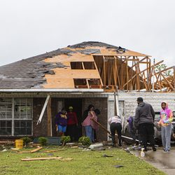 Neighbors and family help to clean a damaged home in Monroe, La. after a tornado ripped through the town just before noon on Sunday, April 12, 2020.