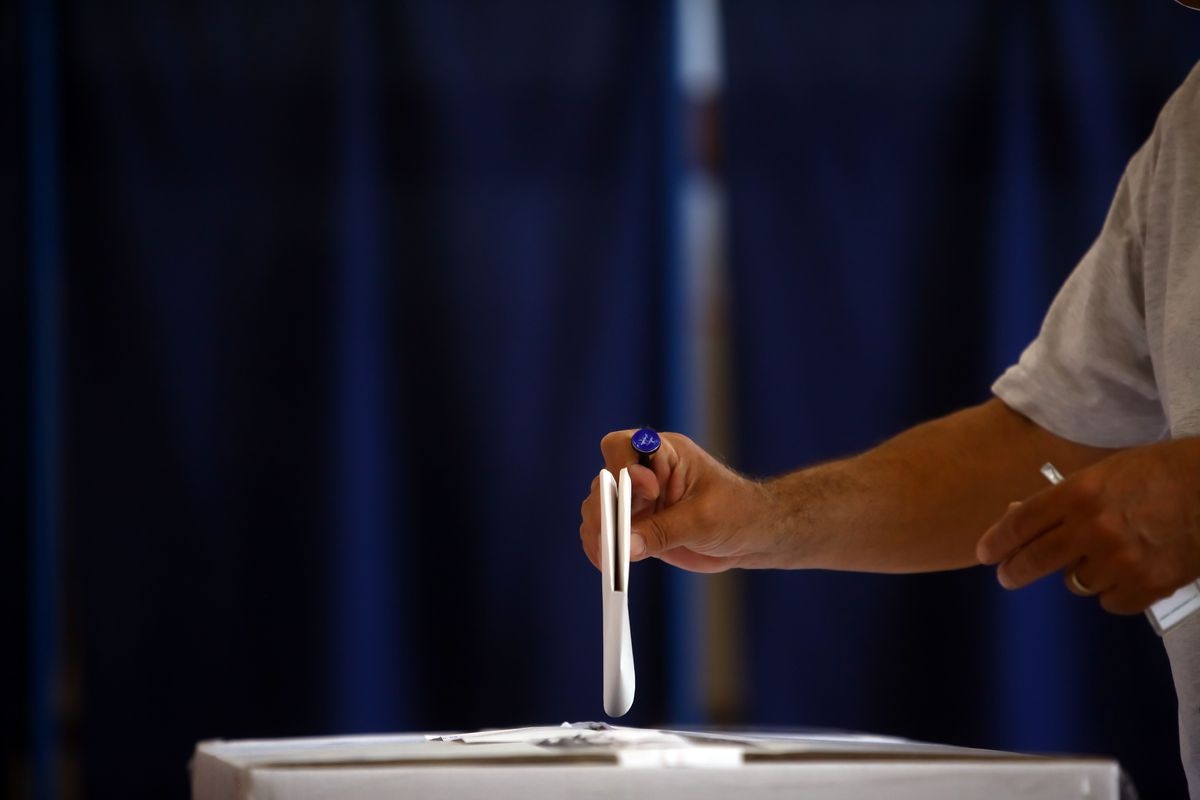 Man drops a ballot into a ballot box