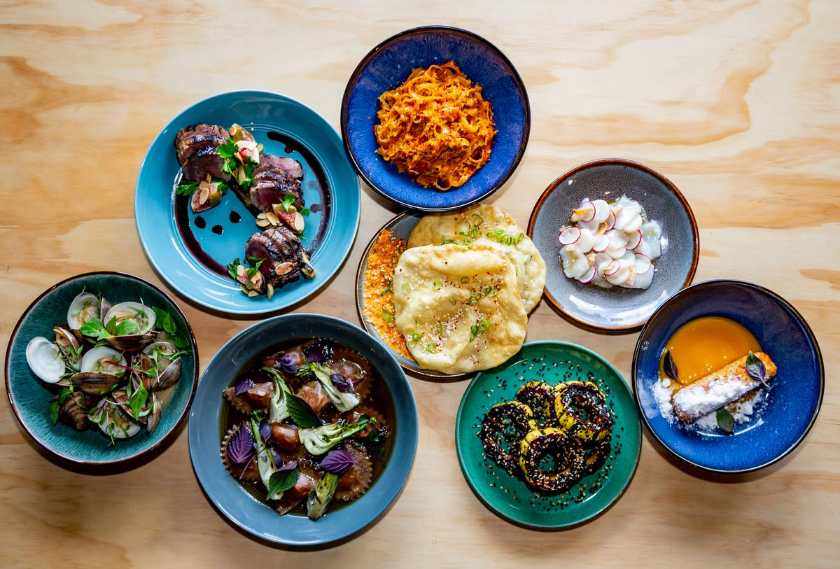 Left to right: Sapelo clams, grilled pork with fig olivada, braised duck mezzelune, herbed taglierini, fry bread, delicata squash, scallop crudo, and coconut sticky rice with mango puree