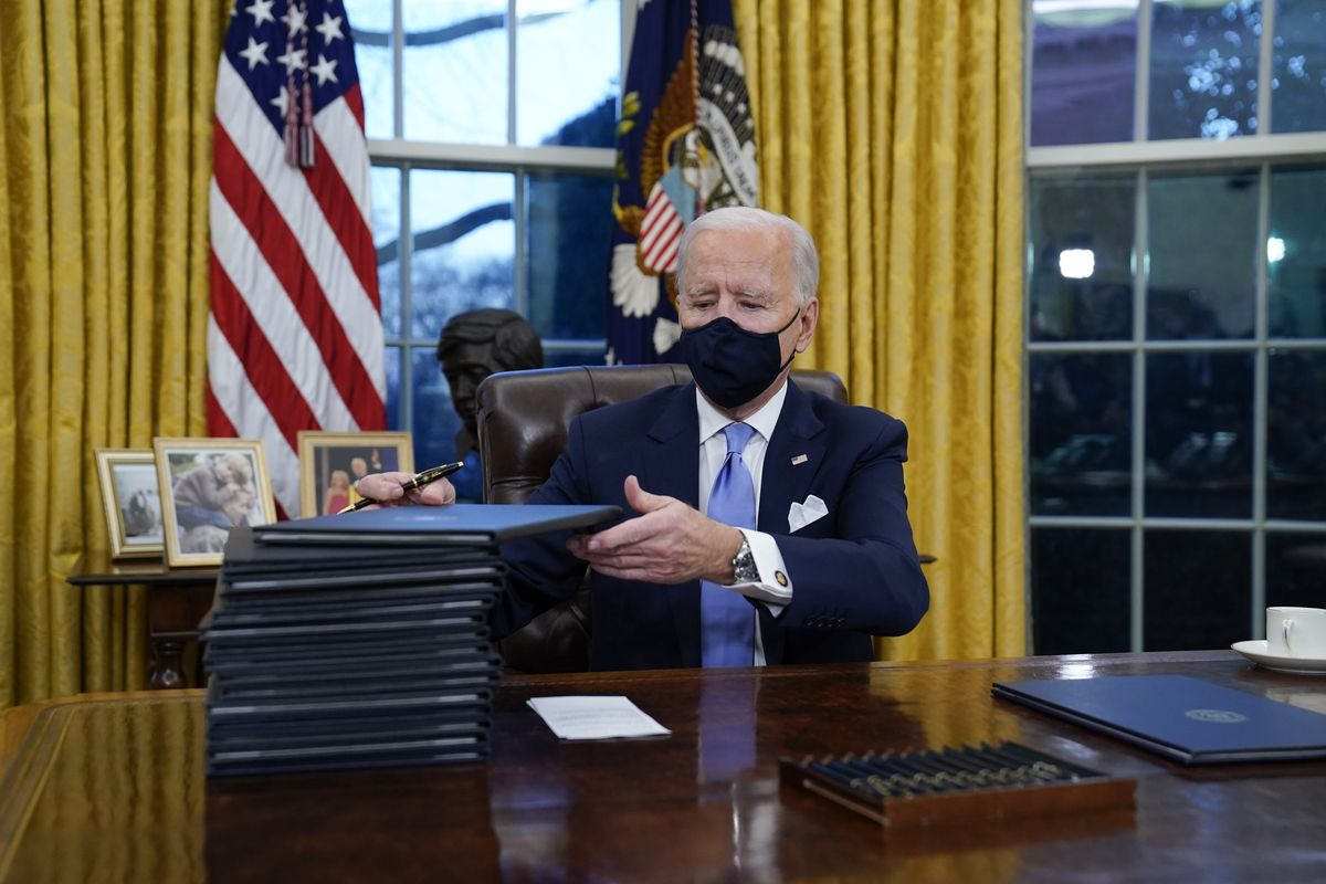 President Joe Biden signs his first executive orders in the Oval Office of the White House on Wednesday, Jan. 20, 2021,