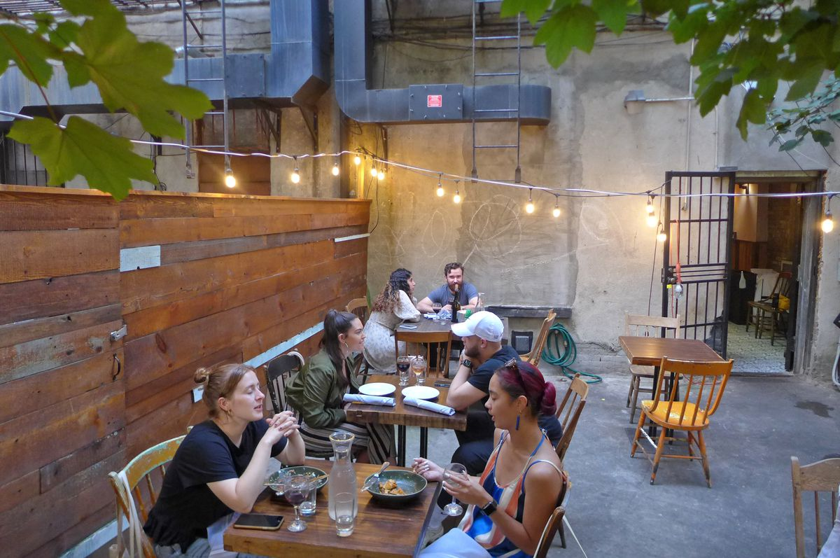 A concrete backyard with a row of occupied tables and wooden fence surrouding.