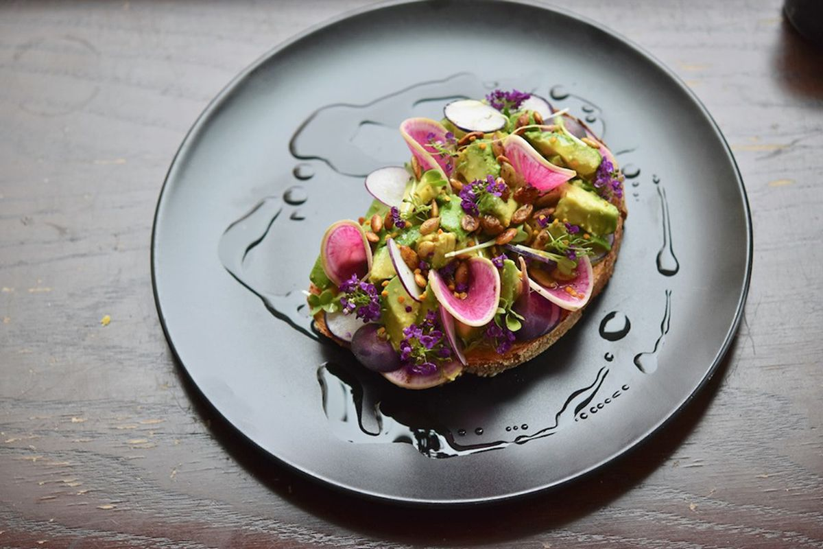 A picture of a slab of toast with curled slices of watermelon radish, pepitas, and avocado