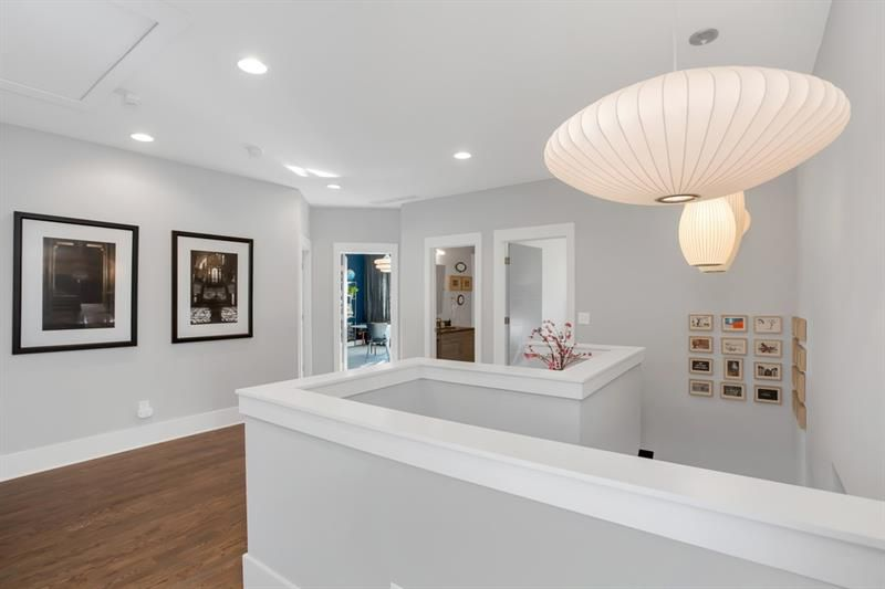 A white landing with much art on the walls on all sides.