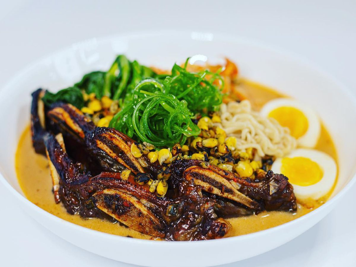 A bowl of brightly colored ramen in broth, with grilled kimchi, seaweed, soft boiled egg, and other fixins