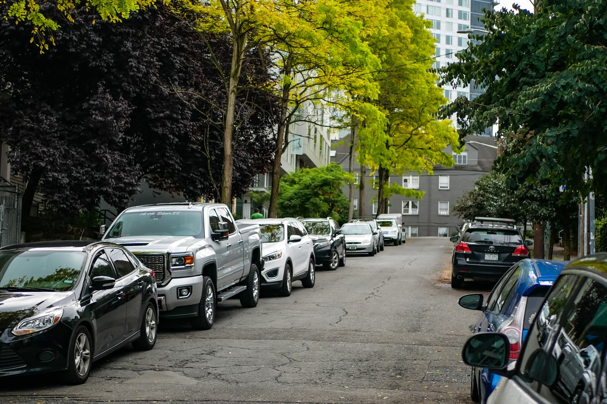 A tree-lined street in Seattle with lines of cars parked