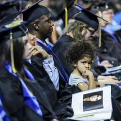 Salt Lake Community College graduate Meckell Gilot sits with his daughter during the 2017 commencement ceremony at the Maverik Center in West Valley City on Friday, May 5, 2017.