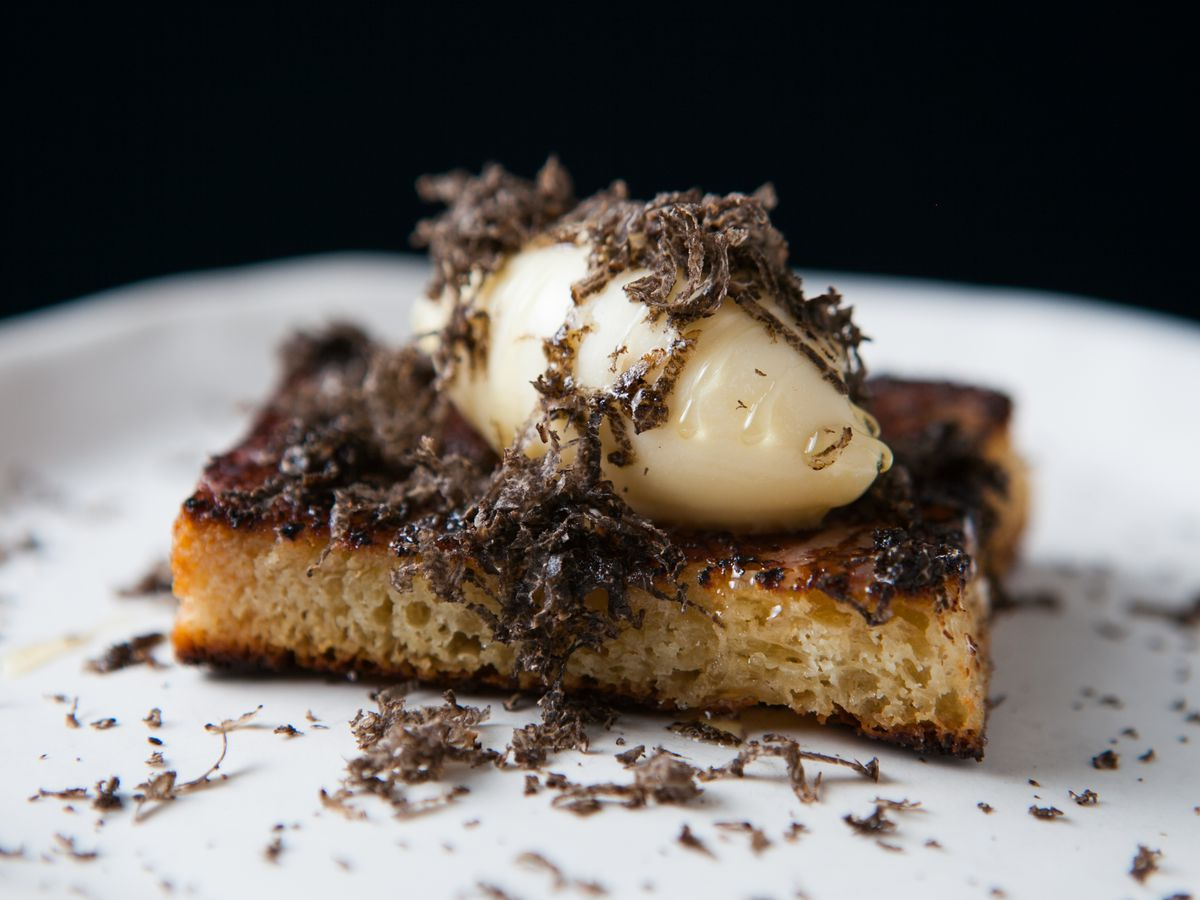 A rectangle piece of milk bread on a white plate with a scoop of ice cream and microplaned black truffle.