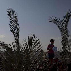 A Christian youth holds a balloon as pilgrims participate in the traditional Palm Sunday procession on the Mount of Olives, overlooking Jerusalem's Old City, Sunday, April 1, 2012. Palm Sunday marks for Christians, Jesus Christ's entrance into Jerusalem, when his followers laid palm branches in his path, prior to his crucifixion.
