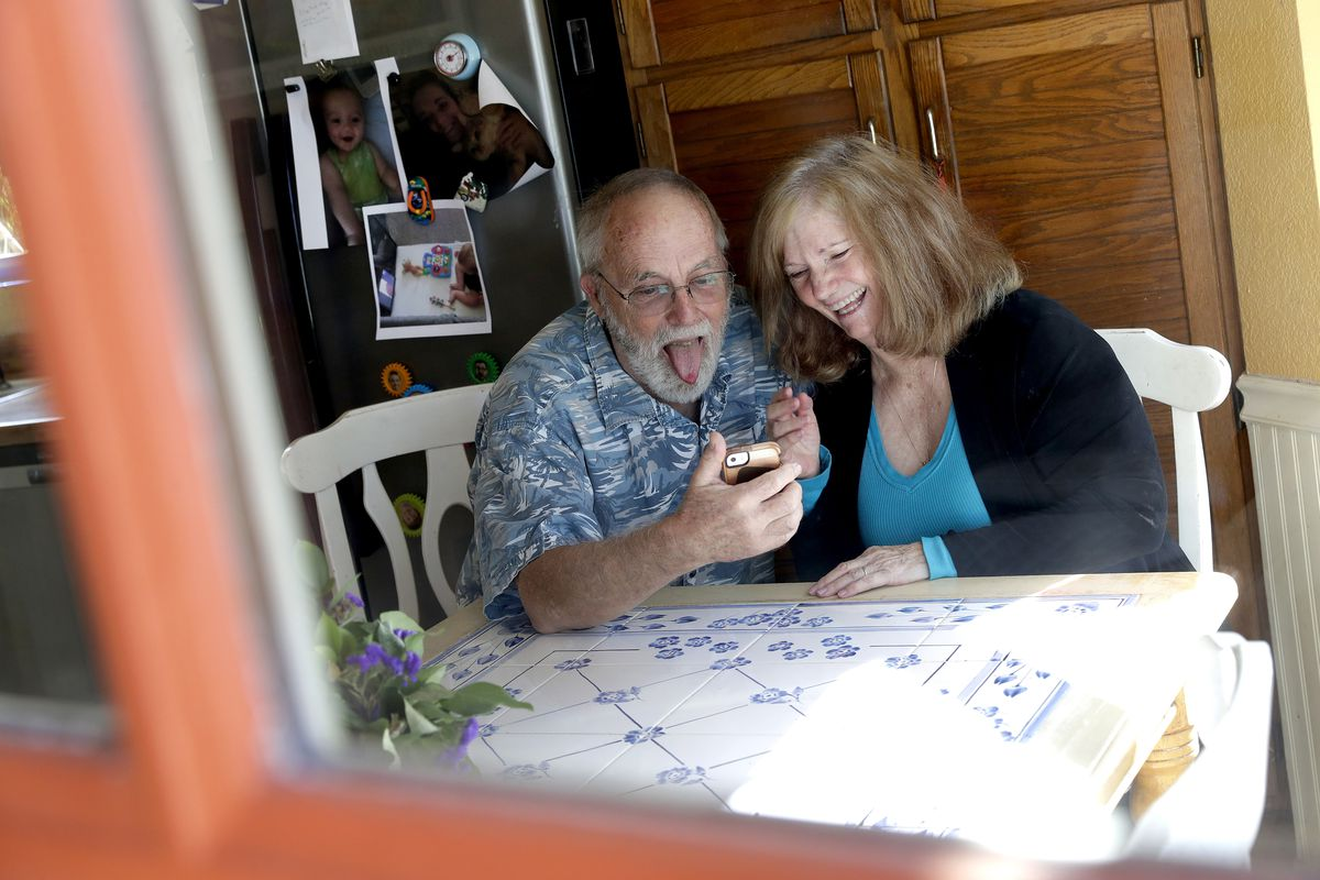 Seen through their kitchen window, Allan and Debbie Cameron contact their grandchildren via the internet. Debbie, 68, has asthma which makes her one of the people most at risk from the new coronavirus.
