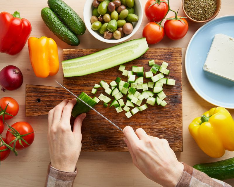 Cucumbers, bell peppers, tomatoes, olives and onions are key ingredients for a healthy and delicious chopped salad.