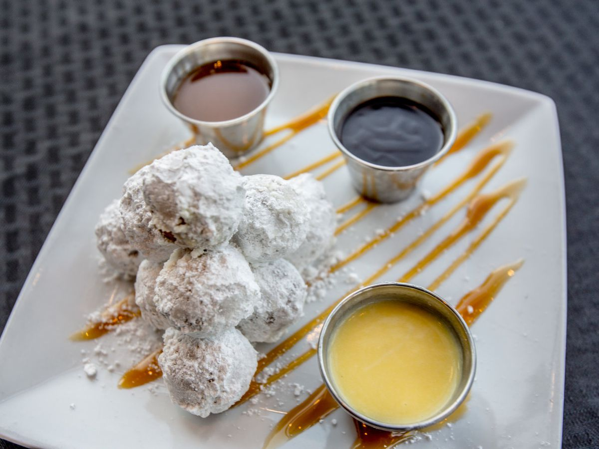 Powdered sugar-covered doughnut holes, next to various sweet dipping sauces