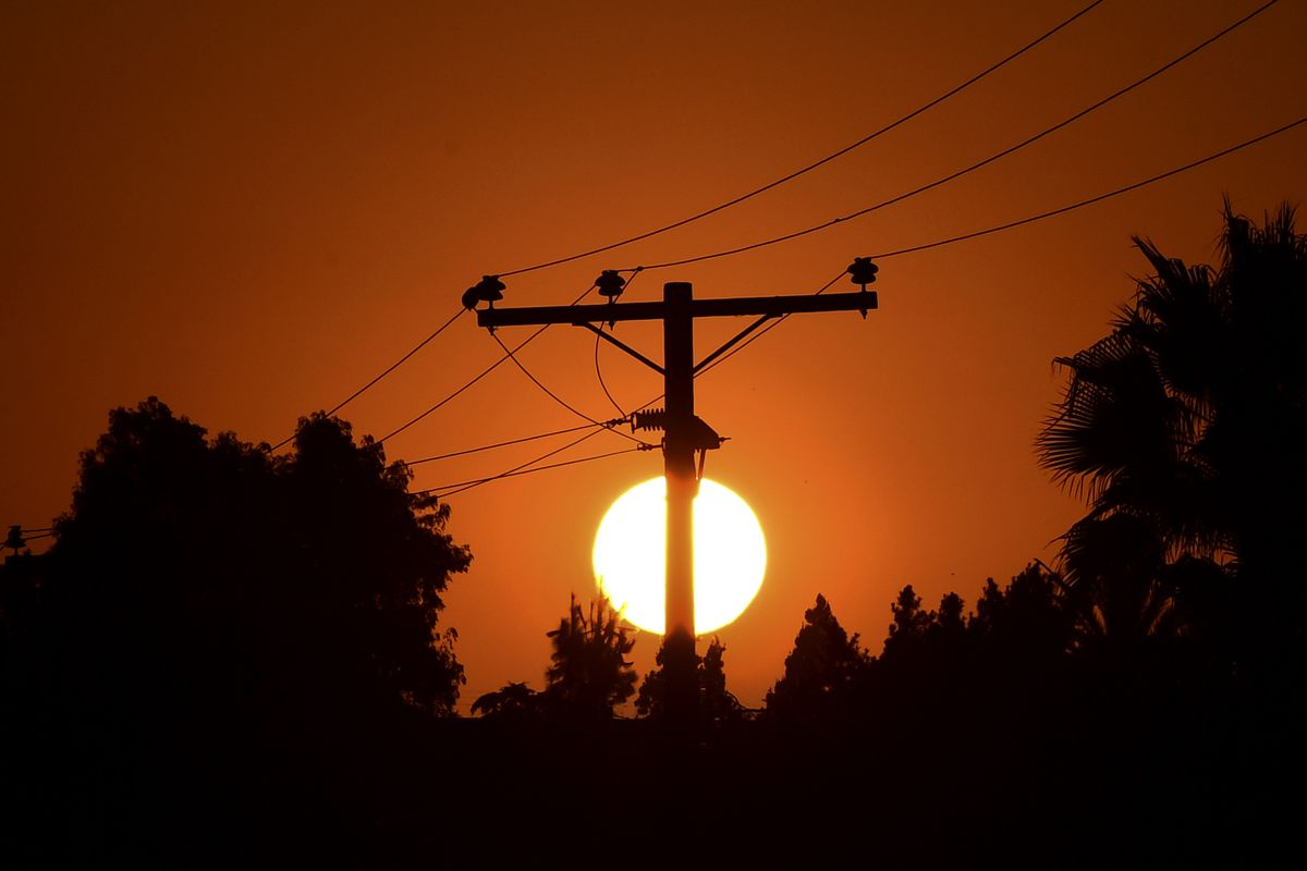 Power lines and trees silhouetted by the setting sun.