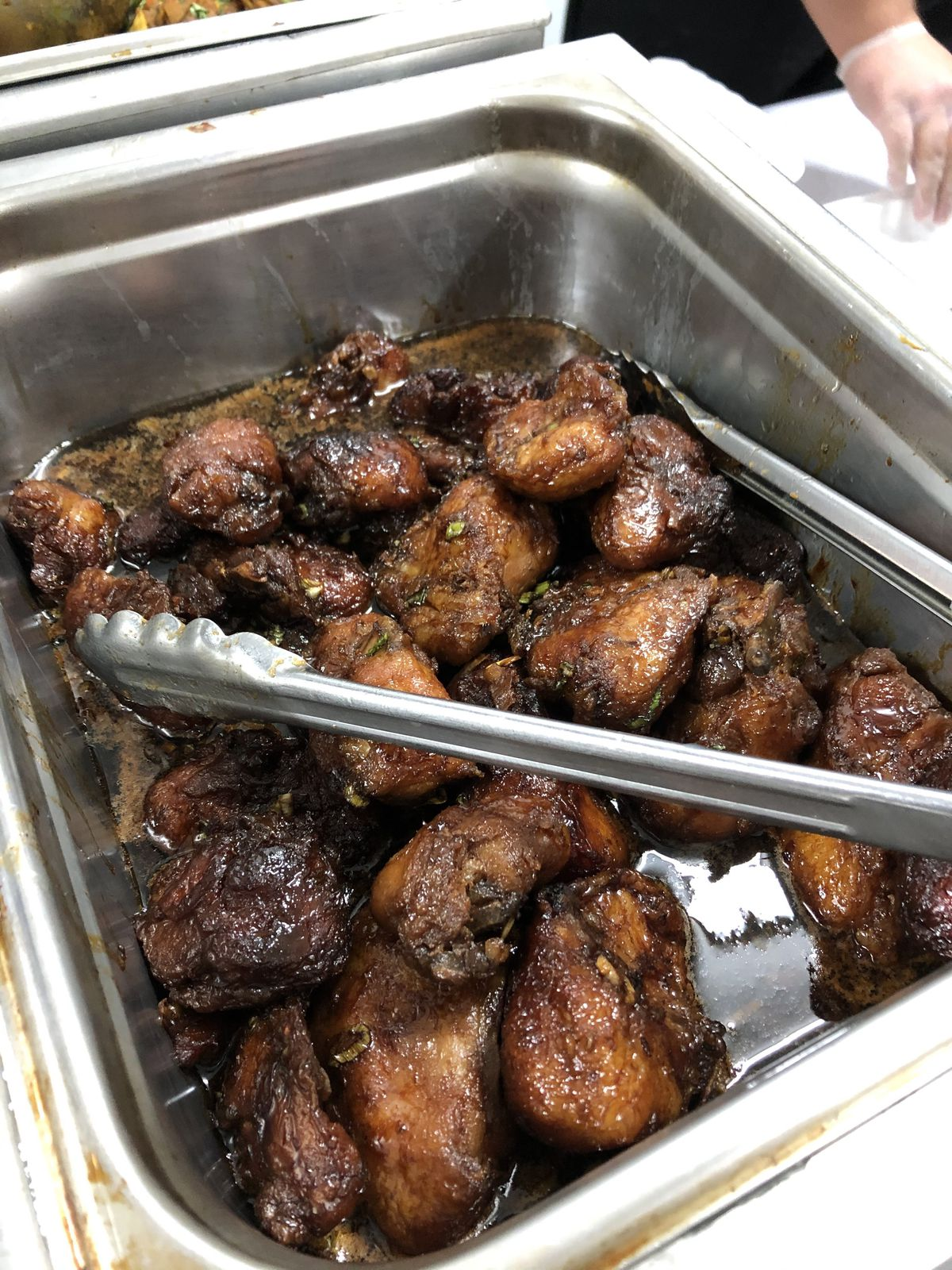 A steam tray of braised turkey tails, cooked until they're very browned and succulent