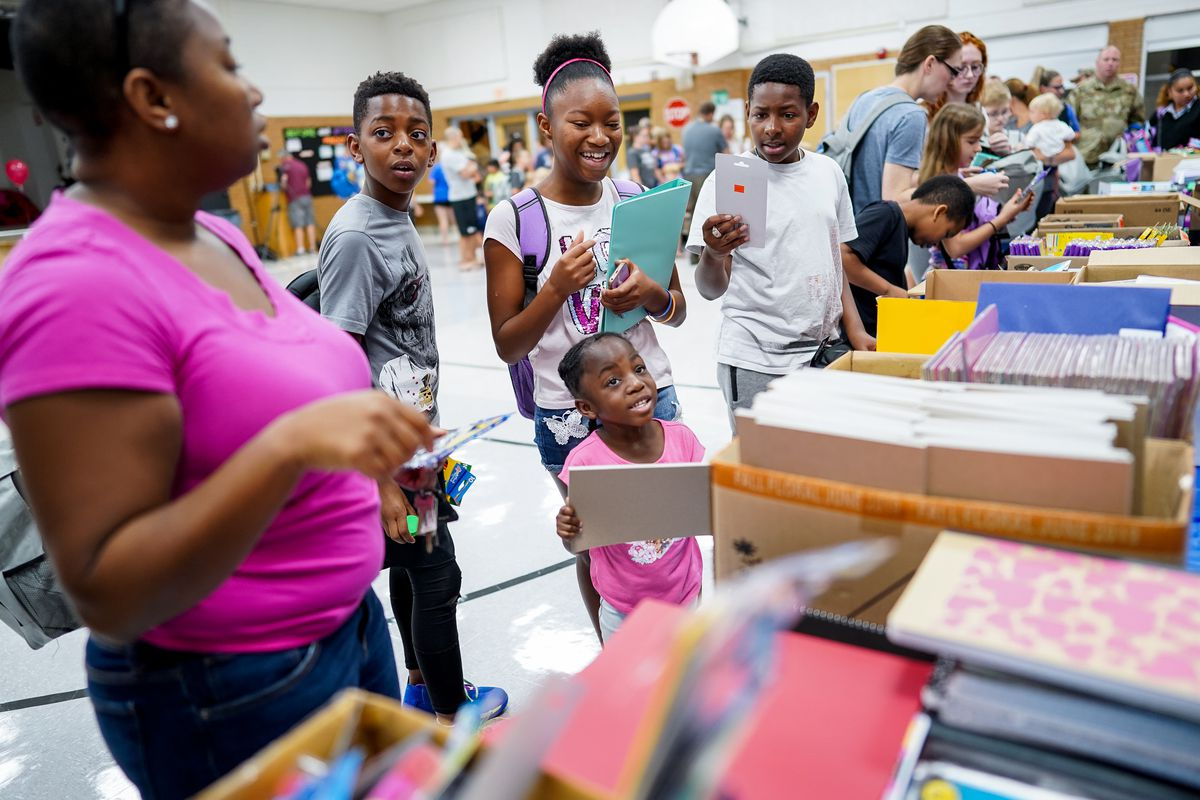 Kimberly Spann and her children, Deon, 10, Arlana, 11, Jordyn, 4, Catrell, 13, Ayden, 9, left to right, and Elijah, 7, not in view, pick out free school supplies during Operation Homefront's annual Back-to-School Brigade event at Hill Field Elementary in Clearfield on Tuesday, Aug. 13, 2019.