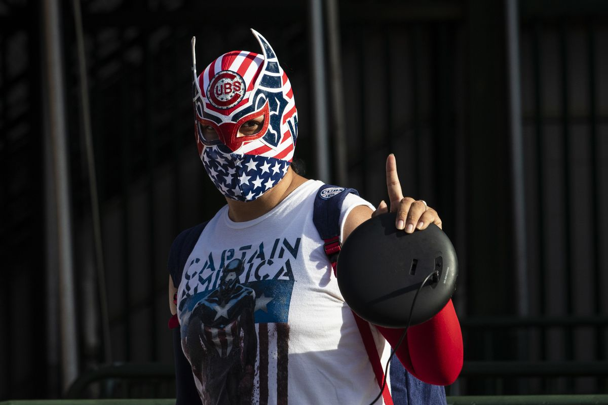 A fan wearing a luchador mask walks by Wrigley Field shortly before the start of the opening day game between the Chicago Cubs and the Milwaukee Brewers, Friday evening, July 24, 2020.