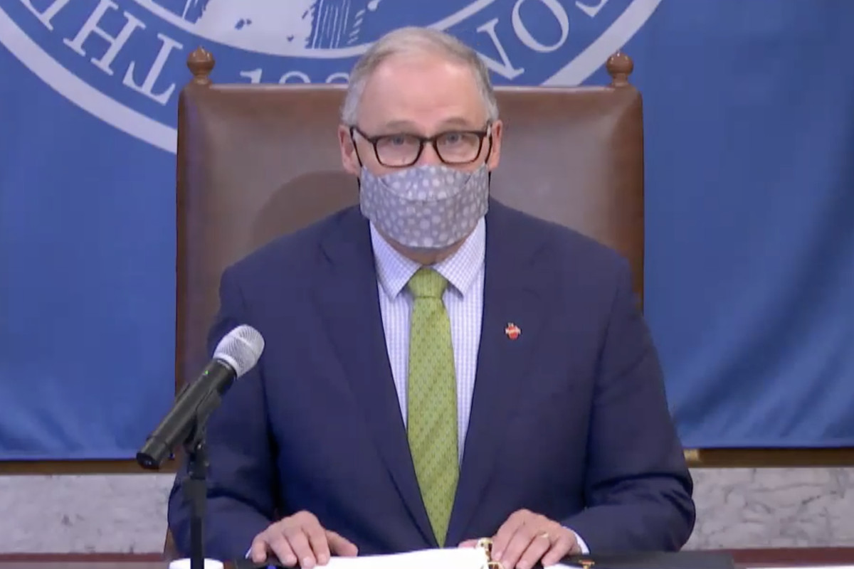 Gov. Jay Inslee at a press conference wearing a light purple face mask and lime green tie