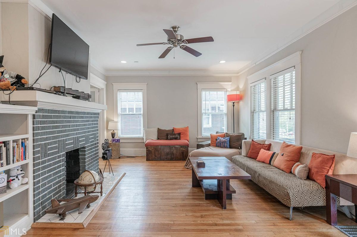 A large living room space with a gib brick fireplace.