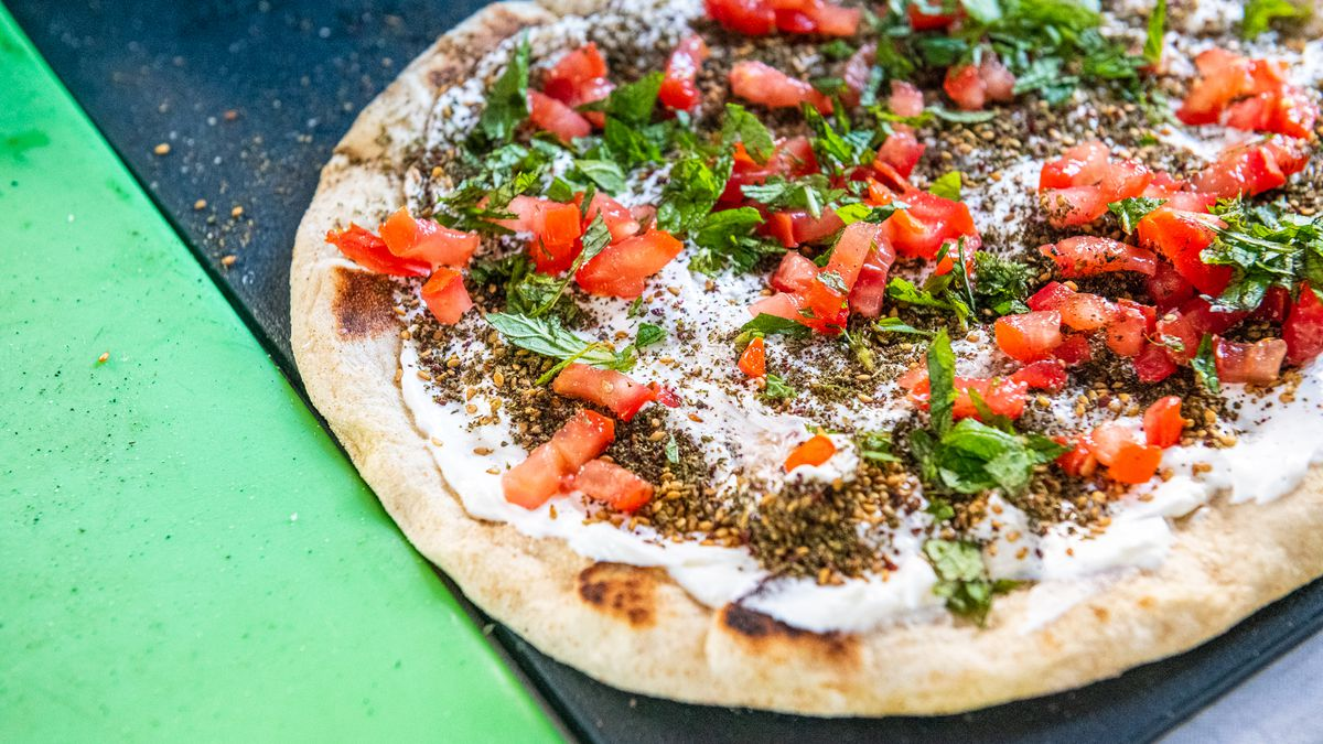 A close-up of Z&Z's manoushe (flatbread) with its brand of za'atar, white strained yogurt, red tomatoes, and green herbs
