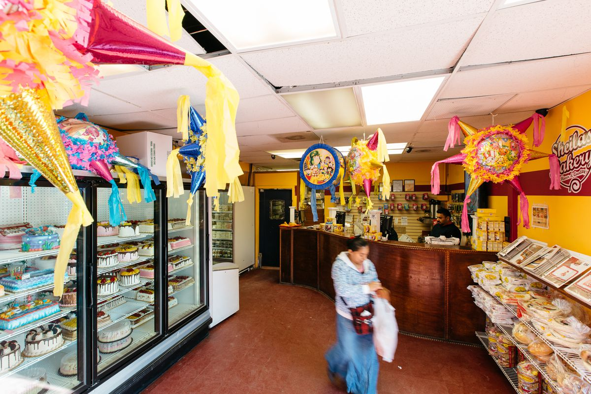 A woman walks out of Sheila's past refrigerated cases full of cakes carrying a plastic bag full of pastries.