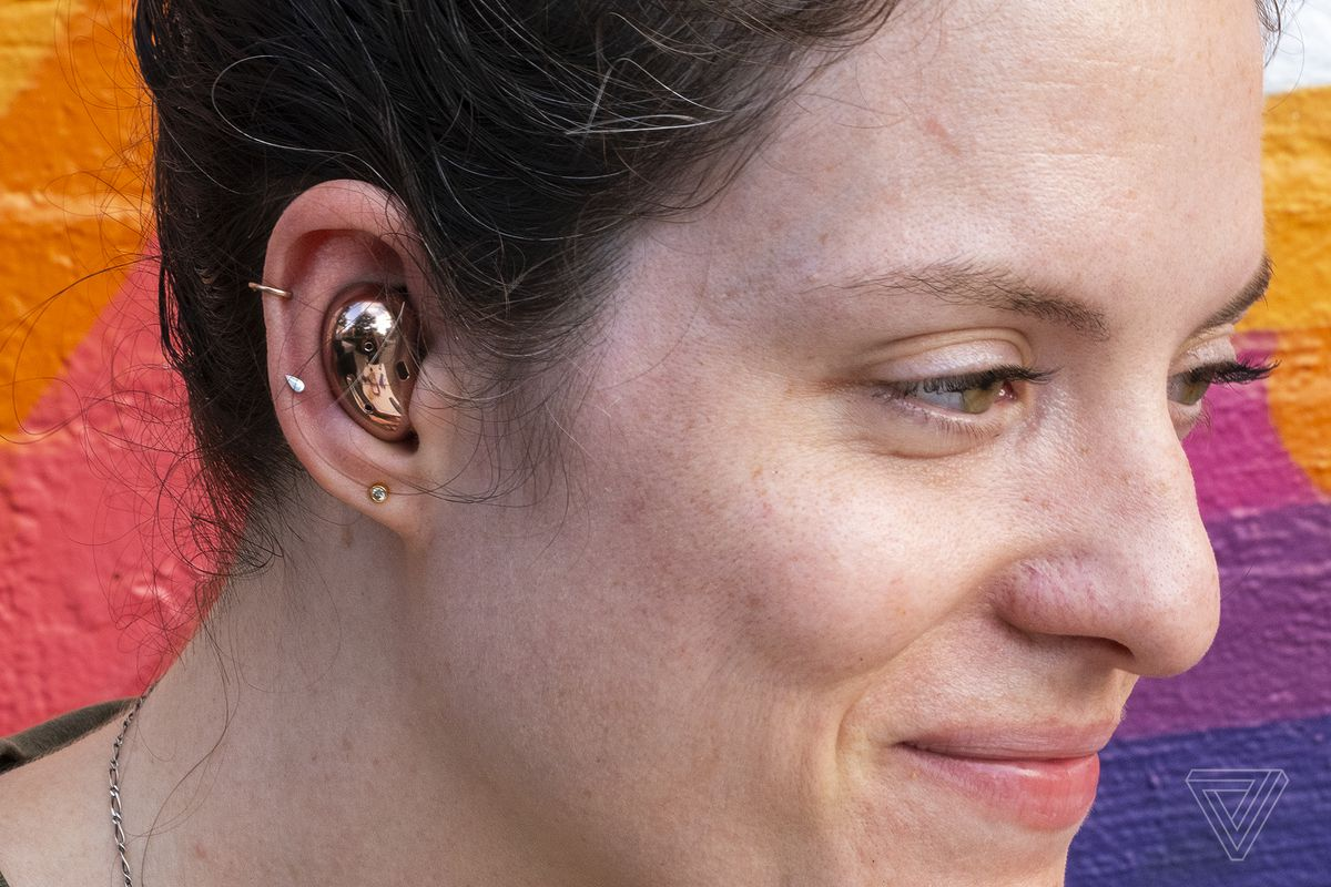 A photo of Samsung's Galaxy Buds Live in someone's ear.