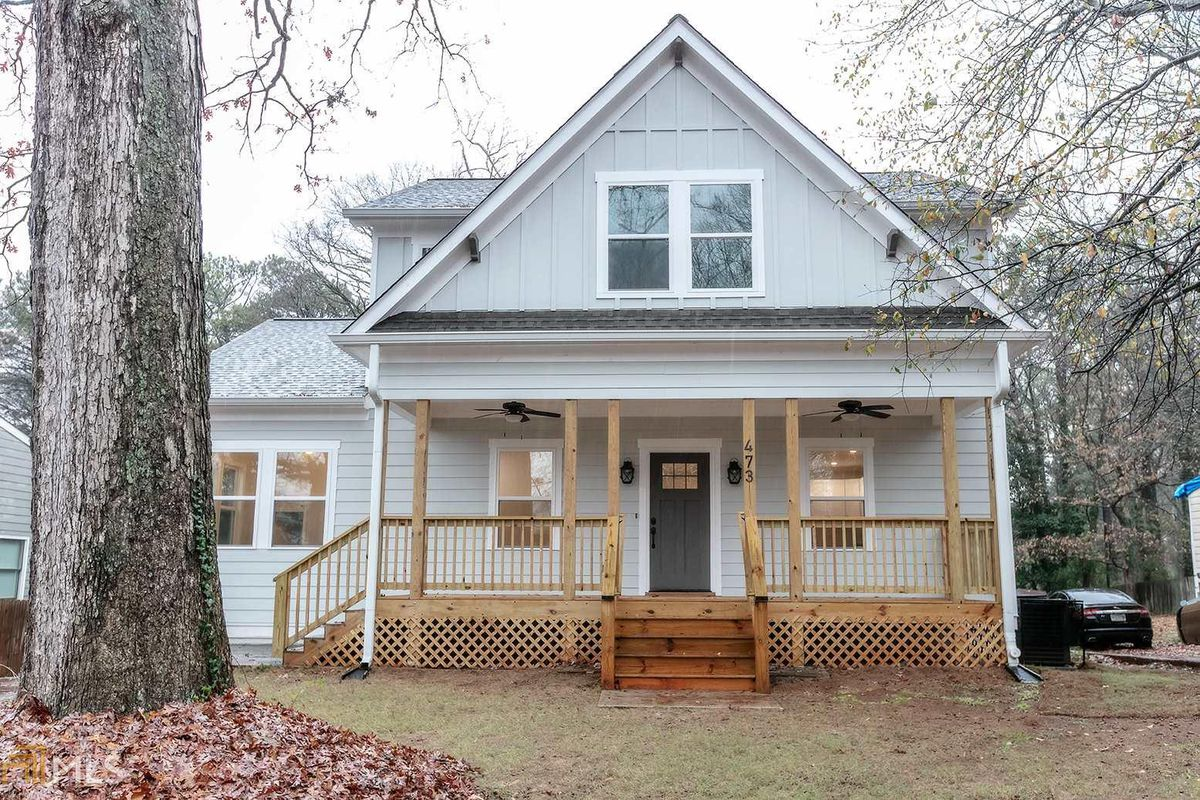 Gray house with covered front porch and tree in yard.