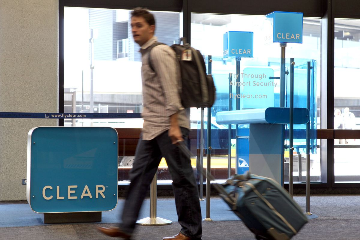 An airline passenger pulls luggage past a Clear kiosk.