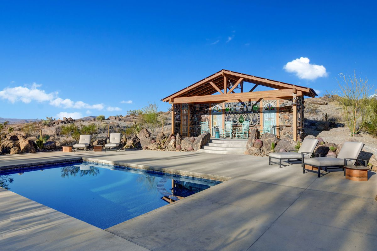 A pool house and saltwater pool sit in a desert landscape.