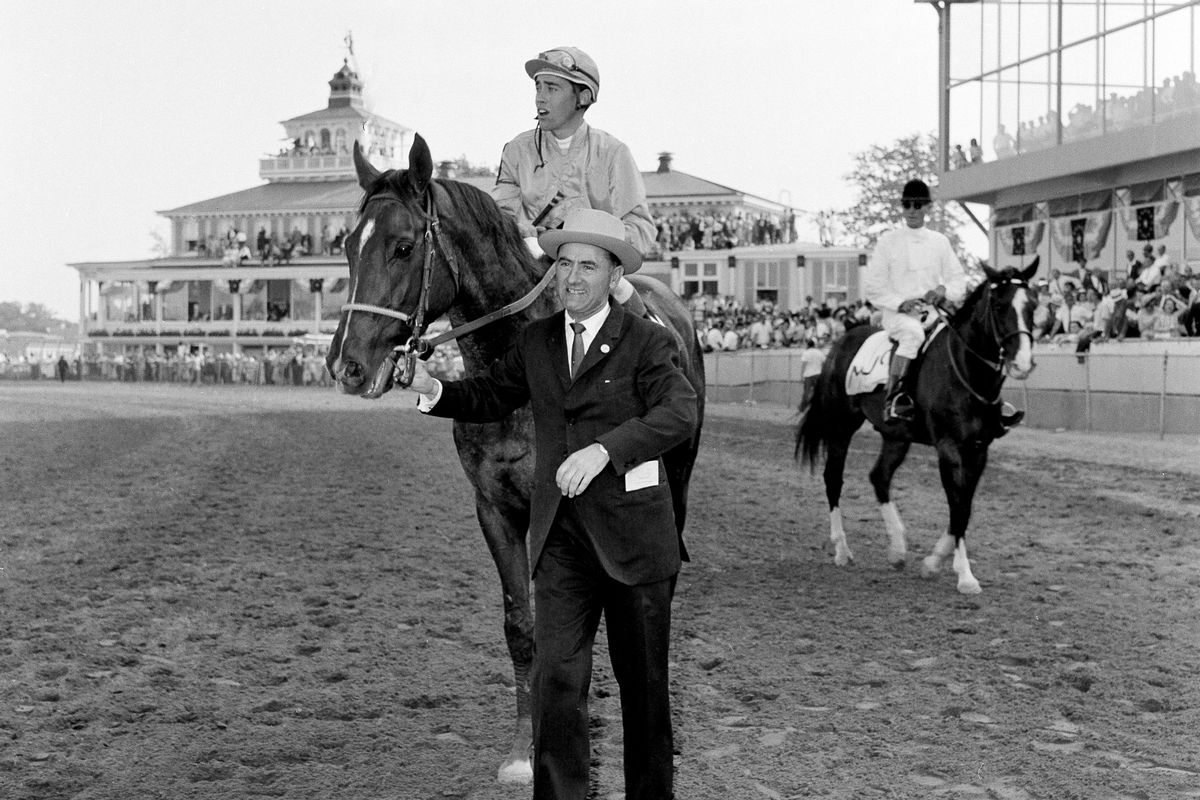 Trainer Virgil Raines leads Greek Money and jockey John Rotz to the winner's circle after winning the 85th Preakness Stakes in this May 19, 1962, file photo. Rotz, a Hall of Famer, has died at 86.