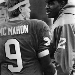 Then Philadelphia Eagles quarterbacks Jim McMahon, left, and Randall Cunningham confer on the sidelines during a game.