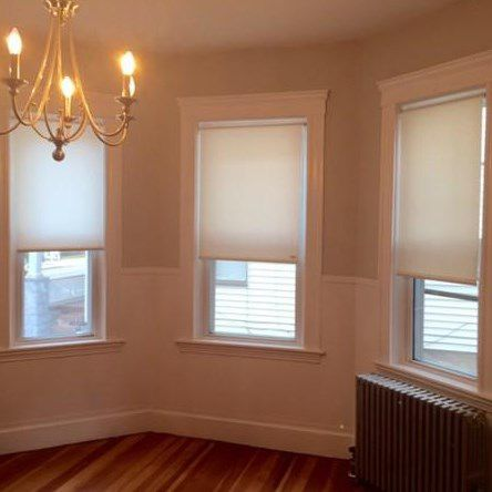 An empty living room portion with the bay window figuring prominently.