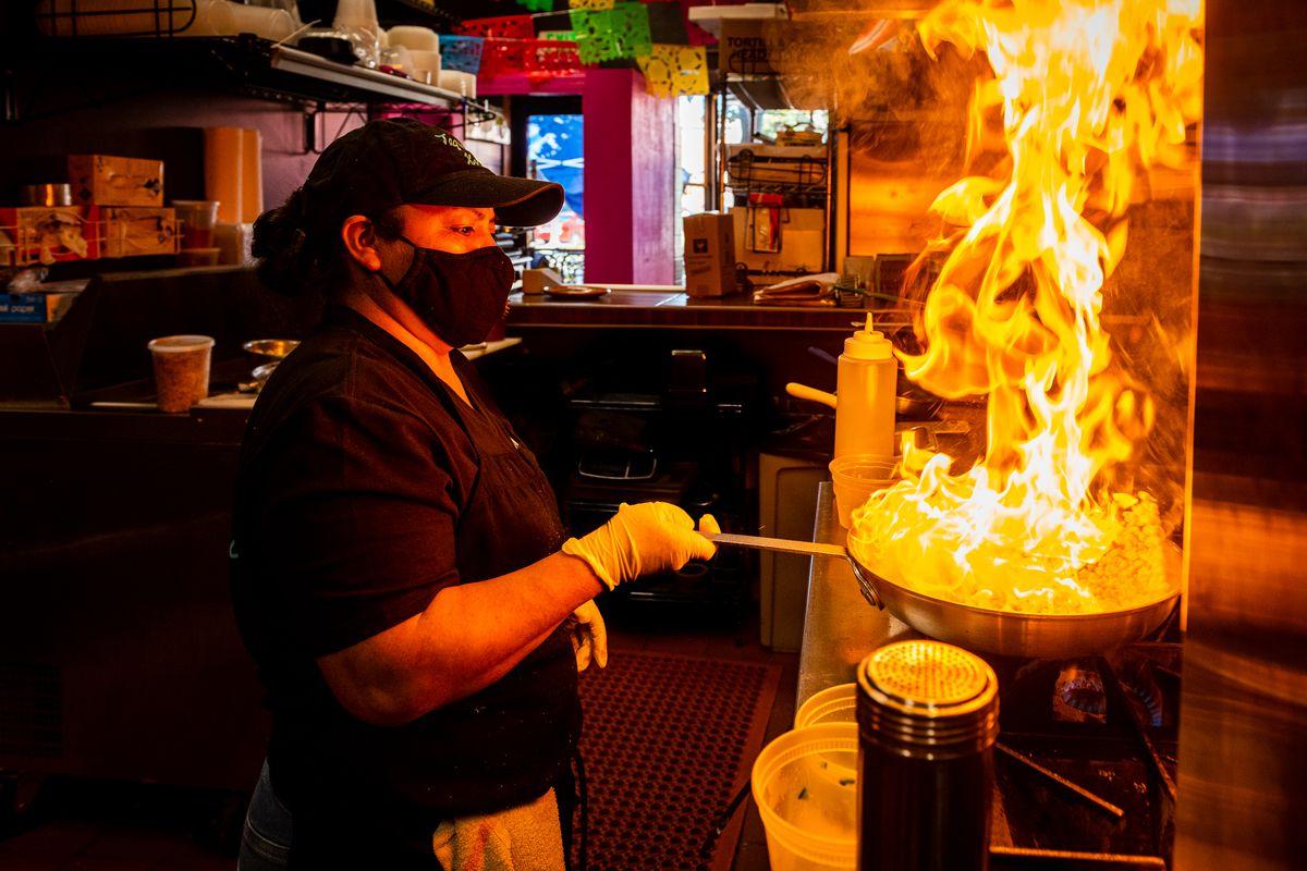 Chef-owner Teresa Padilla flips a pan of corn kernels to make esquites