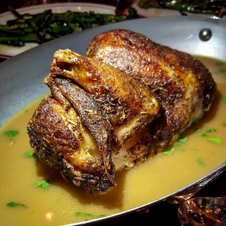 Rotisserie chicken on a plate in a pool of sauce