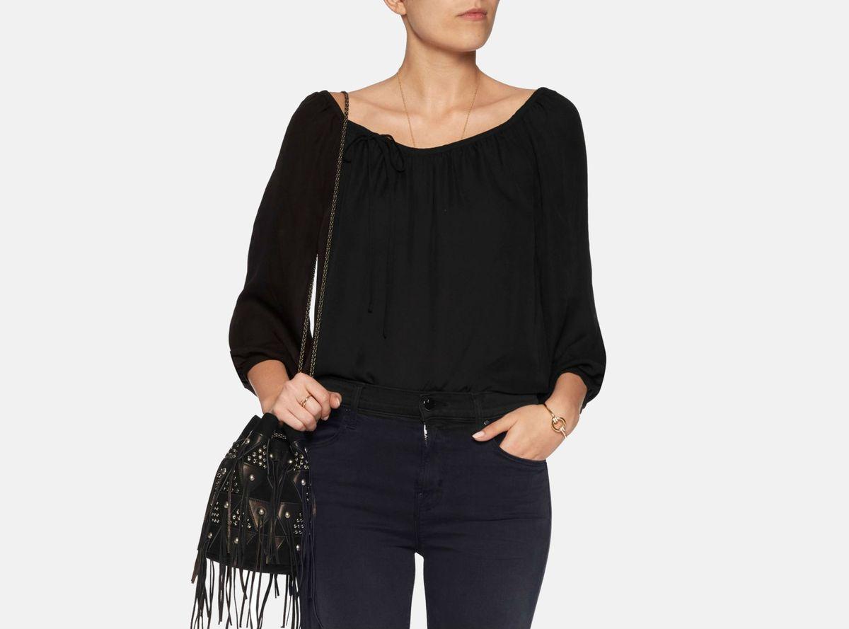 A model in a black off-the-shoulder top