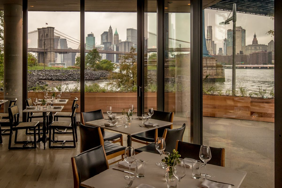 An indoor dining room offers views of a city skyline, waterfront, and bridge overhead through floor-to-ceiling windows