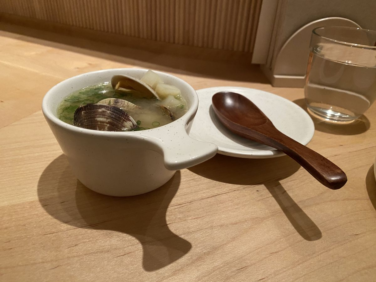 A bowl of clams in broth and a wooden spoon