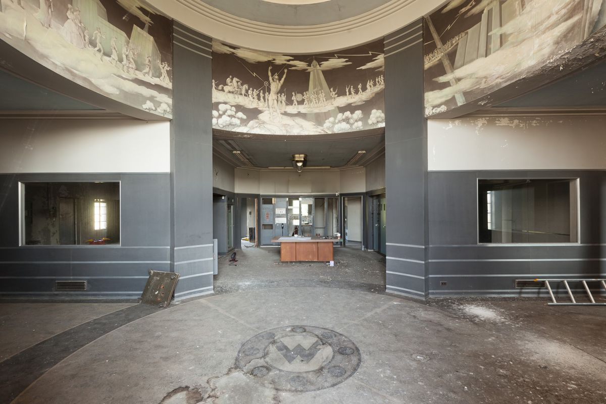 The interior features a circular center room with three corridors leading off to the right, left, and front. At the top of each corridor are strips of Art Deco style paintings with people walking in a line and riding horses. One man raises his arms in fro