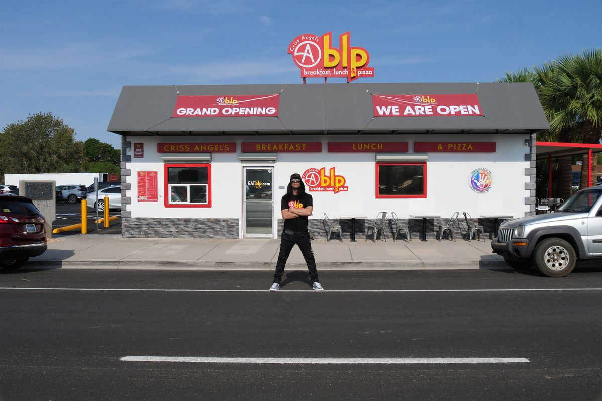 A man stands with his arms crossed in front of a restaurant
