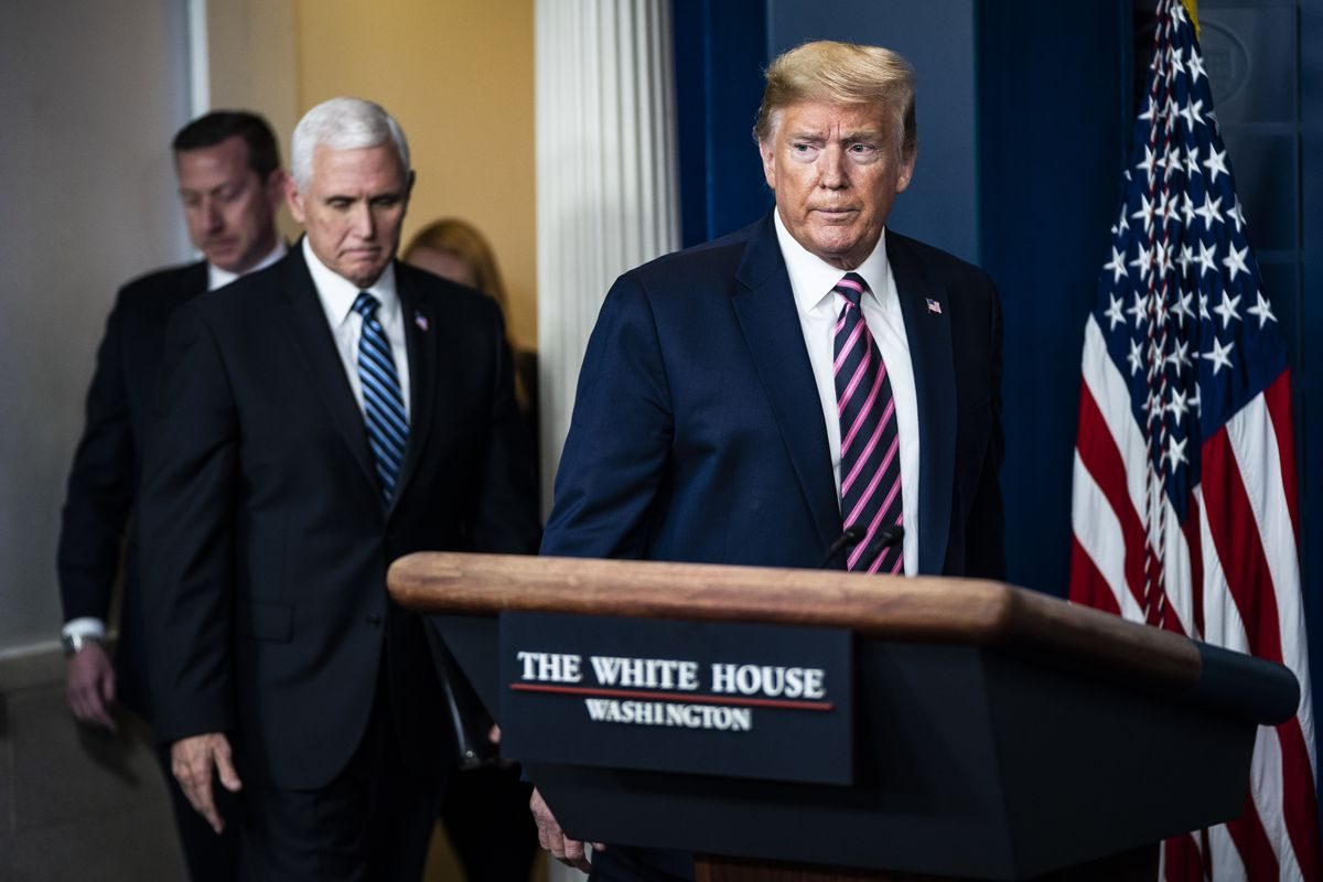 """Trump, in a navy suit and pink and blue striped tie, frowns as he approaches a podium bearing a placard reading """"The White House."""""""