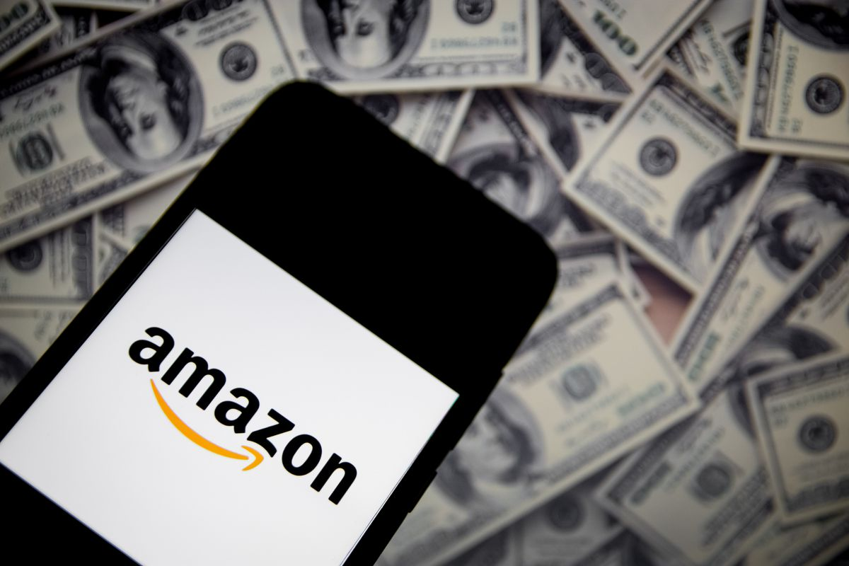 Photo illustration of an Amazon logo on a smartphone laying on top of US dollar bills.
