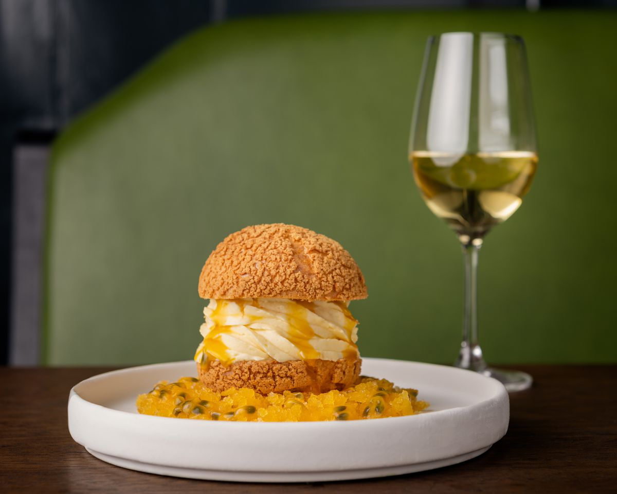 A white plate with a custard bun filled with passion fruit cream and a glass of wine on the side.
