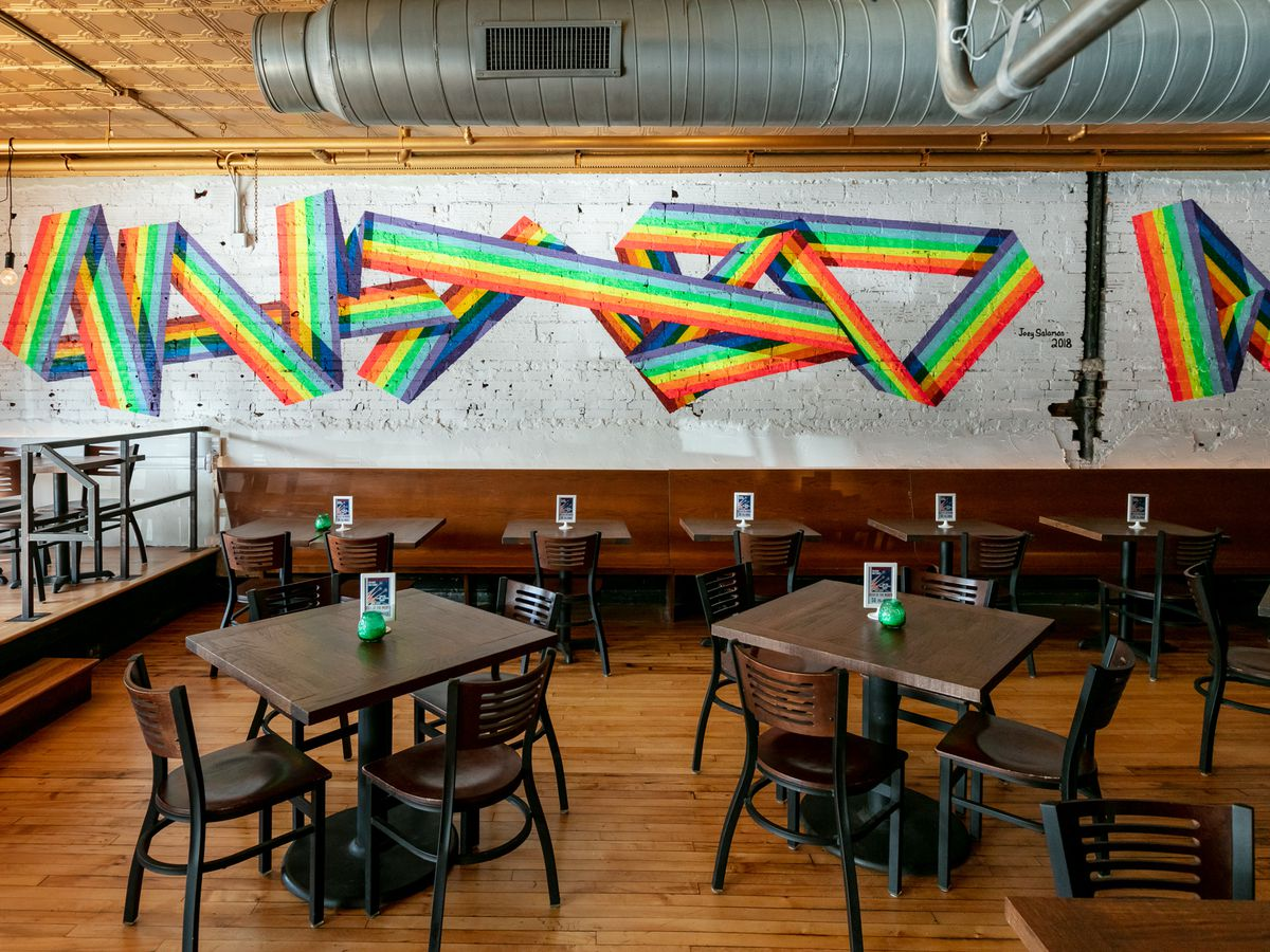 A colorful rainbow mural line on the wall inside Bobcat Bonnie's Ferndale.